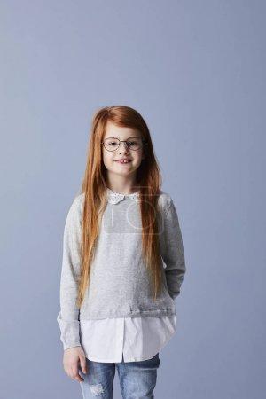 Redhead girl in grey top wearing glasses, smiling at camera