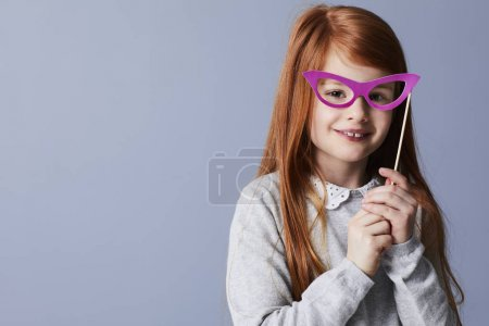 Redheaded girl with pink mask glasses smiling at camera