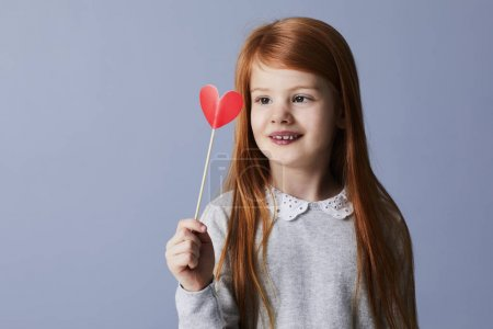 Redheaded girl holding red paper heart on stick