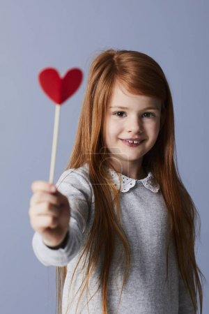 Redheaded girl holding red paper heart on stick showing it at camera