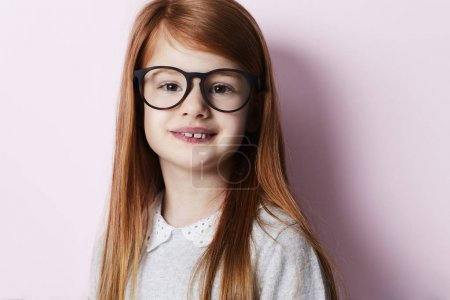 Portrait of redheaded girl in glasses on pink background