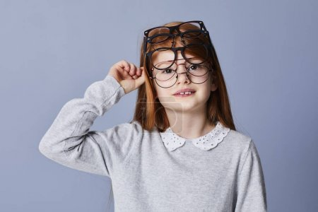 Redheaded girl wearing many glasses, portrait