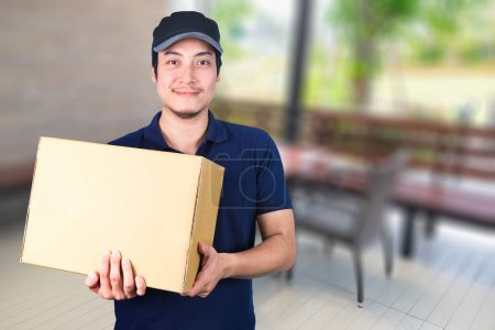 Asian smile Delivery man with cardboard box in hand standing on