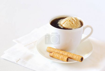 Black coffee with ice cream and chocolate stick