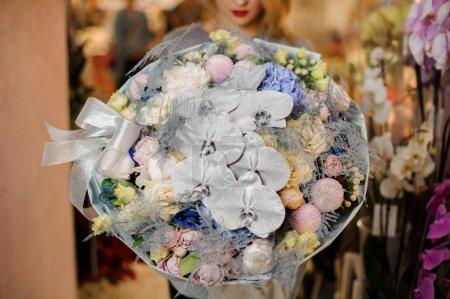 Photo pour Fille dans un pull gris tient un énorme bouquet de fleurs différentes, y compris les orchidées argentées, hortensia bleu, roses violettes décorées d'arc argenté - image libre de droit