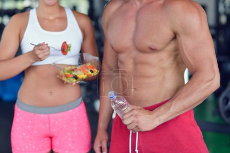 couple of bodybuilders eating at gym