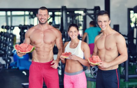 bodybuilders eating watermelon at gym
