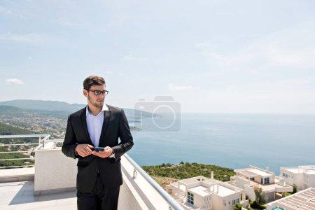 Photo pour Portrait de jeune homme en costume décontracté debout sur le toit et utilisant le téléphone portable, la mer bleue et les bâtiments de l'hôtel en arrière-plan - image libre de droit