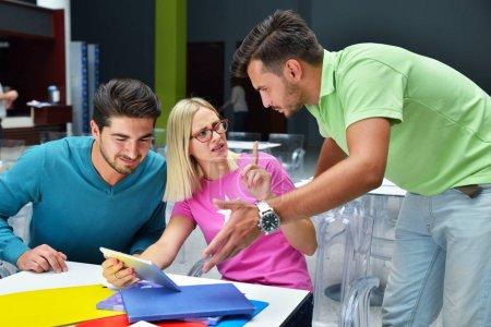 Photo pour Groupe d'étudiants assis dans un café avec des livres et tablette numérique et regarder des photos - image libre de droit