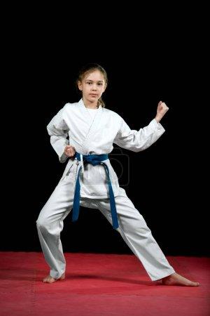 One little girl in white kimono during training karate kata exercises