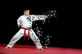 One little boy in white kimono during training karate kata exercises