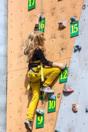 Little rock climber on climbing wall