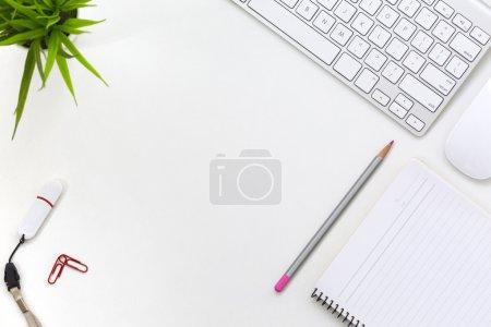 Photo pour Vue de dessus de plat Lay Office du milieu du travail sur une Table blanche avec clavier d'ordinateur portable et souris blanc Page du cahier rouge trombones et ordinateur lecteur flash - image libre de droit