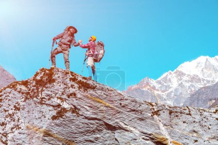 Photo for Two Hikers of different age staying on high Rock in Mountains enjoying Scenery with copy space in blue sky - Royalty Free Image