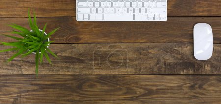 Photo for Office Workplace on natural wooden handcrafted Table with Laptop Keyboard and Mouse green Flower - Royalty Free Image
