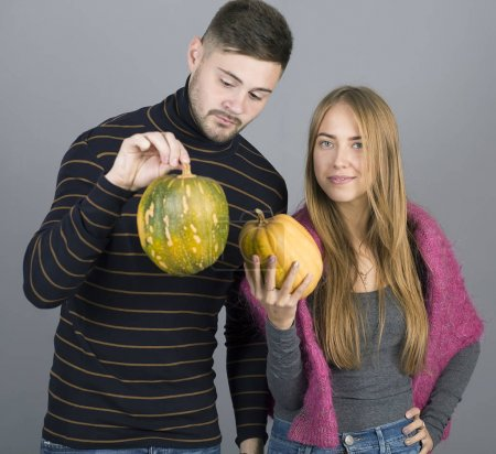 Young man and girl holding pumpkins