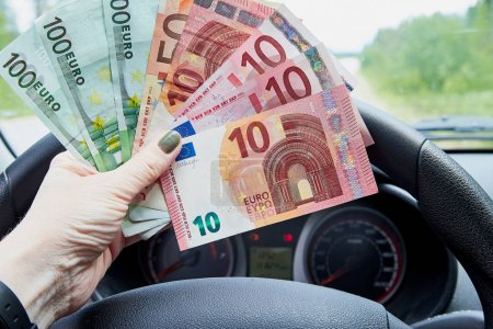 Photo for Euro banknotes of various denominations in a woman hand inside of a car and road with nature outside - Royalty Free Image