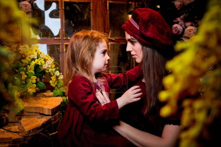 Photo for Easter. Family models in rural wooden interior with flower in studio. Mother and daughter in maroon or red dresses of the village shepherdesses - Royalty Free Image