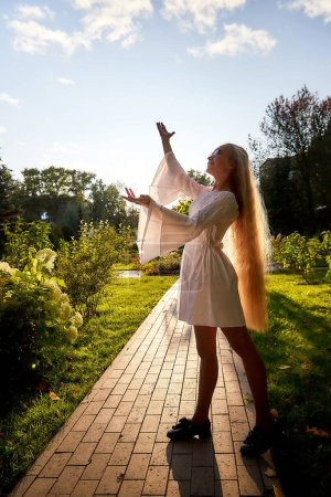 Photo for Pretty teenage girl 14-16 year old with curly long blonde hair dancing in the green park in a summer day. Beautiful outdoors portrait - Royalty Free Image