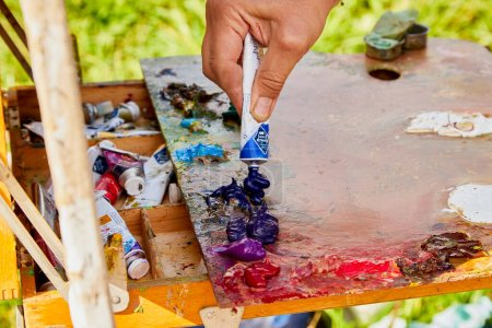 Photo for Male hand of artist, palette with paints and canvas in nature outdoors and greenery background in a summer sunny day - Royalty Free Image