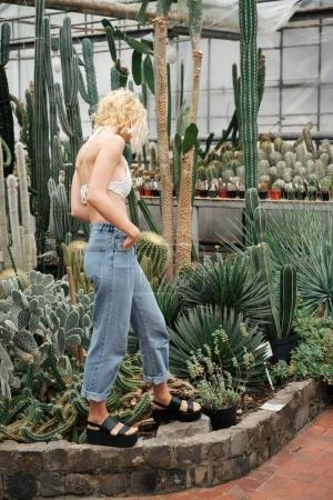 Beautiful blonde woman walking in cactus and succulent plants