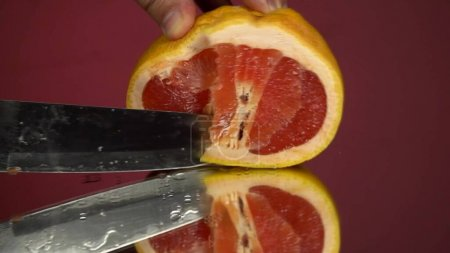 Grapefruit fillets and half of a red grapefruit a on the mirror and red background, on the mirror fillets and half of a red grapefruit a on the mirror and red background, on the mirror