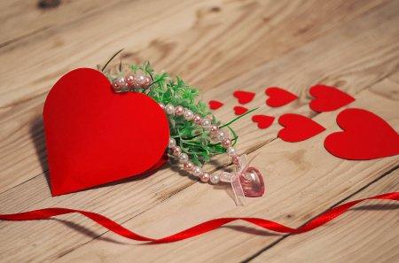 Photo pour Coeurs, fleurs, rubans sur un fond clair en bois - image libre de droit