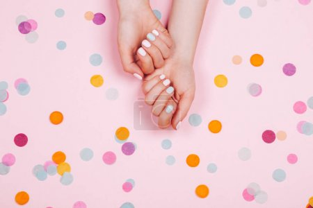 Photo for Stylish trendy female pink and blue manicure. Beautiful young womans hands on pink pastel background with festive multicolored confetti. - Royalty Free Image