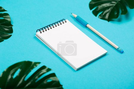 Photo for Spiral notepad with pencil as mockup for your design. Note book on pastel blue background. Tropical leaves sa a decor. - Royalty Free Image