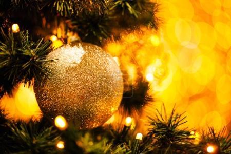Foto de Rama de abeto con bola y luces festivas en el fondo de Navidad con destellos . - Imagen libre de derechos