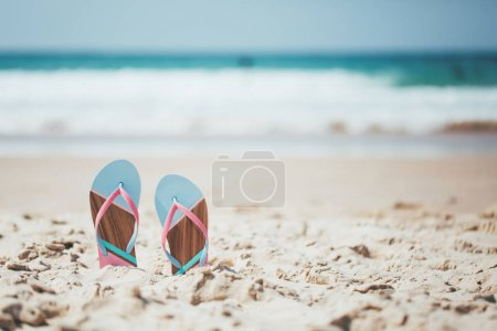Photo for Trendy, blue and pink slippers on white sandy ocean beach. - Royalty Free Image