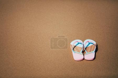 Trendy slippers on the sandy beach.