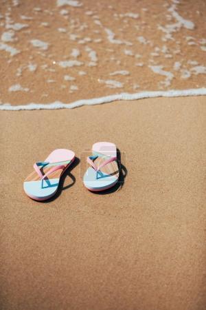 Trendy slippers on the sandy beach.