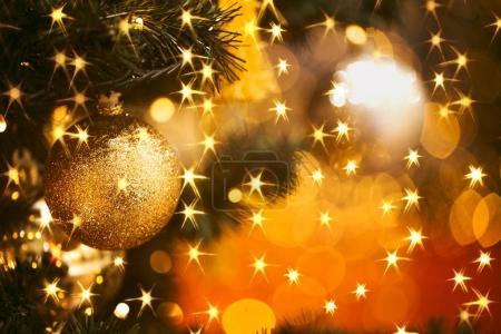 Photo pour Branche de sapin avec des boules et des lumières festives sur le fond de Noël avec des étincelles . - image libre de droit