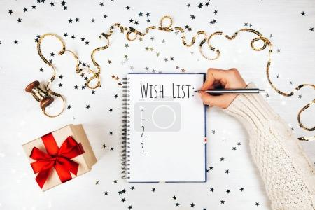 Holiday decorations and woman writing opened notebook on white rustic table, flat lay style. Christmas planning concept.