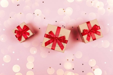 Three presents with red bow on pastel trendy pink background with little silver sparkles. Flat lay style. Christmas lights overlayed