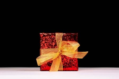 Red gift box with golden ribbon over black backdrop. Front view.