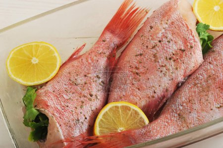Raw seabass stuffed with parsley and lemon in a gl...