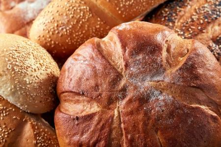 Different kinds of bread and bread rolls on board from above. Kitchen or bakery poster design. Close-up.