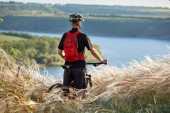 Cyclist with backpack on his mountain bike travel on waterside. Traveler has adventur on meadow on riverside.