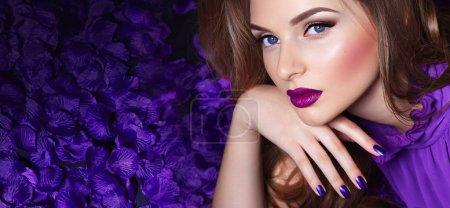 Photo pour La fille aux pétales. Belle jeune fille se trouve dans les pétales violets dans une robe longue. Glamour, luxe. Cheveux - boucles. Maquillage - flèches, rouge à lèvres violet. Amour, romance. - image libre de droit