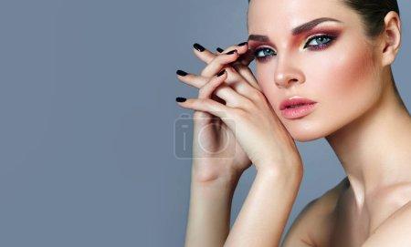 Photo pour Belle jeune fille bien entretenue avec un maquillage brillant et une peau lisse en studio. Portrait. Mode, beauté, cosmétique.Manucure, ac noir pour ongles, belles mains et doigts. - image libre de droit