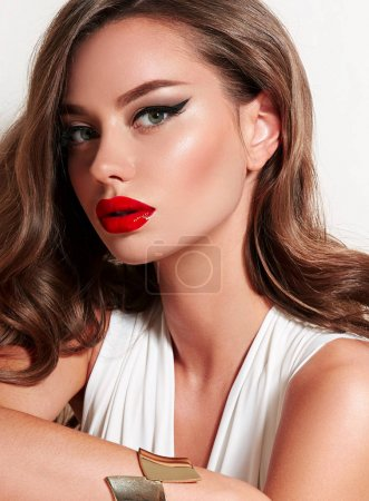 Photo for Beautiful well-groomed girl with a slender body and magnificent shiny hair poses in the studio on a white background.Beauty, fashion, gold jewelry, beauty salon, cosmetics, makeup, clothing. - Royalty Free Image