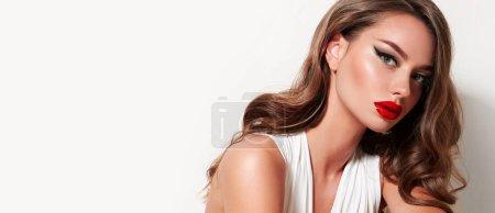 Photo pour Belle fille bien soignée avec un corps mince et de magnifiques poses de cheveux brillants dans le studio sur un fond blanc. Beauté, mode, bijoux en or, salon de beauté, cosmétiques, maquillage, vêtements. - image libre de droit