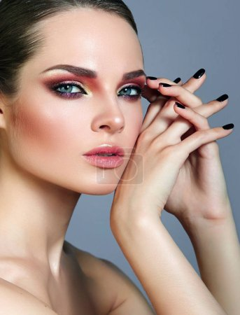 Photo for Beautiful young well-groomed girl with bright shiny make-up and smooth skin in the studio. Portrait. Fashion, beauty, cosmetics.Manicure, black ac for nails, beautiful hands and fingers. - Royalty Free Image