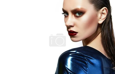 Photo for Girl in latex dress. Red lipstick and red nail polish. Beautiful and effective young girl with bright make-up and wet hair. The shadows are metallic. Fashion, beauty, advertising. - Royalty Free Image