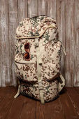Travel backpack with vintage glasses on a wooden background