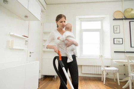 Photo pour Femme frustrée, nettoyage de tapis dans le salon en tenant le nouveau-né dans une main et aspirateur dans un autre, fatiguée femme, combinaison de faire beaucoup de choses, se sent limitant parfois. Concept de ménage à la maison, - image libre de droit