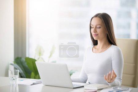 Photo pour Jeune femme près de l'ordinateur portable, pratiquer la méditation au bureau, en face de l'ordinateur portable, des cours de yoga en ligne, prendre un temps de pause pendant une minute, la guérison de la paperasse et le rayonnement de l'ordinateur portable - image libre de droit