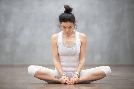 Photo pour Portrait de belle jeune femme avec des tatouages floraux travaillant contre un mur gris, faisant du yoga ou des exercices de pilates, assise en baddha konasana, angle lié, cordonnier, pose de papillon. Plan complet - image libre de droit